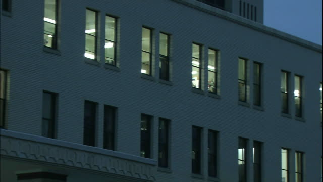 lights shine through row of windows on the Toyama Prefectural Government Office