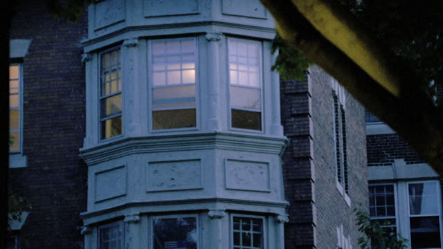 lights shines from inside a bay window of an apartment building in philadelphia. - bay window stock videos & royalty-free footage