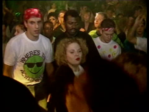 lights spinning in disco acid house / people dancing to 80s music / people wearing ecstasy drug smiley face tshirts / groups of people dancing... - drogmissbruk bildbanksvideor och videomaterial från bakom kulisserna