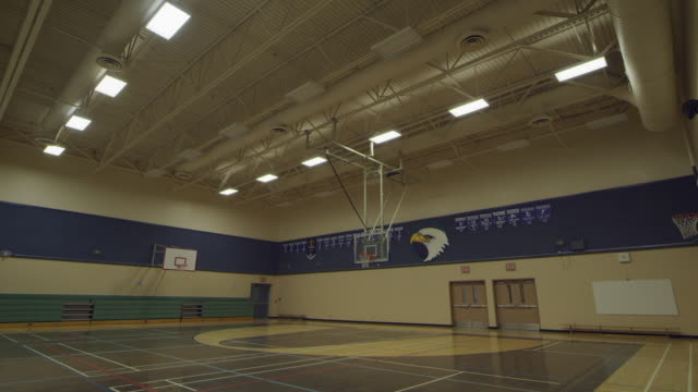 lights turning off in empty school gym - turnhalle stock-videos und b-roll-filmmaterial