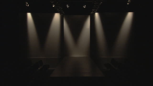 vídeos y material grabado en eventos de stock de ws lights turning on above empty catwalk / london, england, uk - escenario