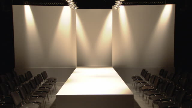 ws lights turning on and off above empty catwalk / london, england, uk - fashion show点の映像素材/bロール