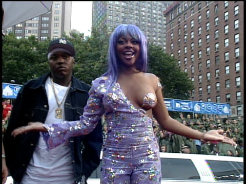vídeos de stock e filmes b-roll de lil' kim with purple hair and wearing a dress exposing her left breast adorned with a purple pasty arriving at the 1999 mtv video music awards red... - 1999