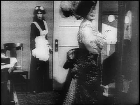 stockvideo's en b-roll-footage met lillian russell wearing big hat posing for camera in dressing room as maid stands at door - huishoudelijke dienstverlening