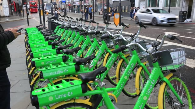lime e bikes for hire parked on the pavement in london, uk. - electricity stock videos & royalty-free footage