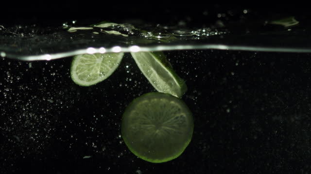 Lime slices drop falling into water, black background