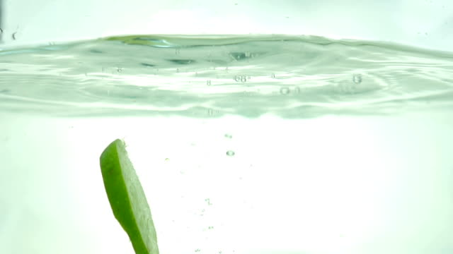 Lime slices drop in the water. Close up. Slow motion.