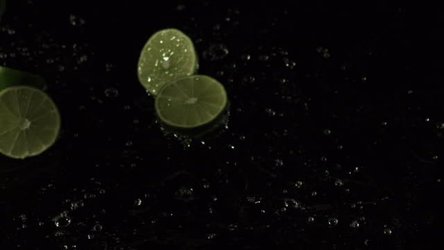 lime slices falling into water, black background - lime stock videos & royalty-free footage