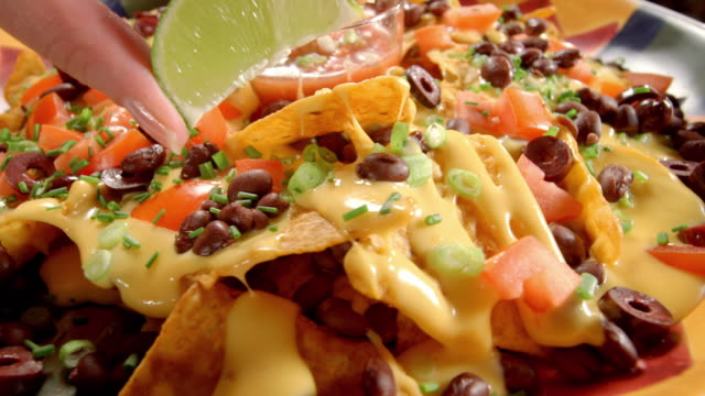 cu lime wedge squeezed over party platter of nachos - mexican food stock videos & royalty-free footage