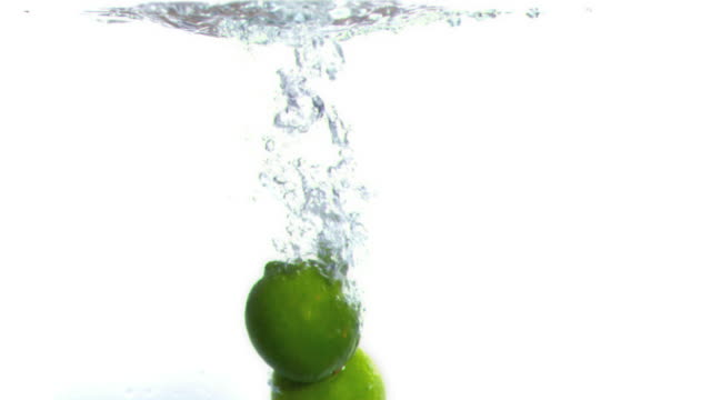 limes falling into water in super slow motion - lime stock videos & royalty-free footage