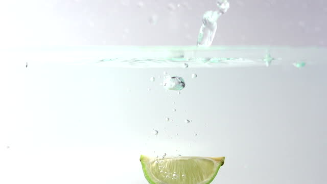 Limes splashing into water