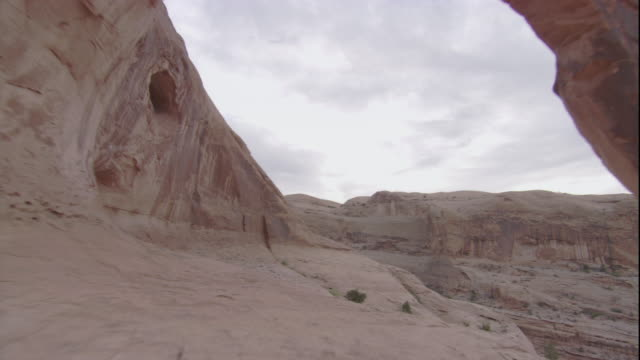 A limestone arch leads to a vast desert canyon in Utah. Available in HD.