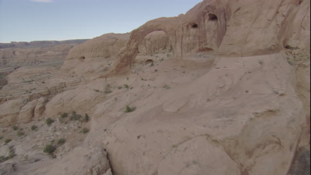 A limestone arch opens onto sheer cliffs in the Utah desert. Available in HD.