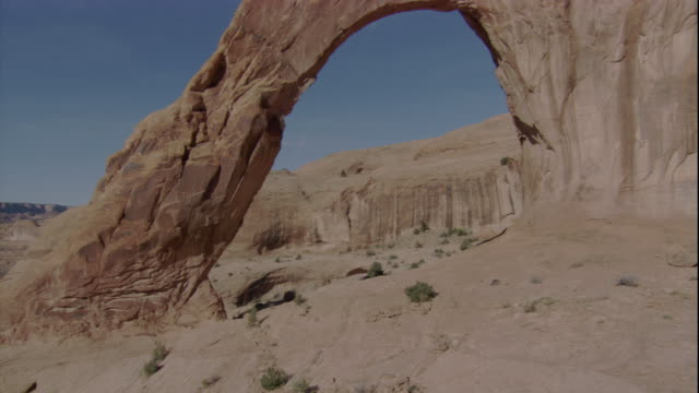 A limestone formation creates a natural arch in a Utah desert. Available in HD.