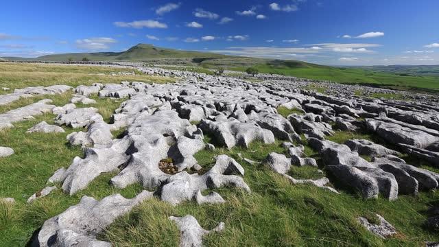 limestone pavement on twisleton scar above ingleton, yorkshire dales, uk looking towards penyghent. - eroded stock videos & royalty-free footage