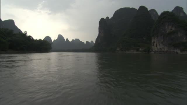 limestone peaks tower above the shoreline of the li river in china's scenic longshen region. - li river stock videos & royalty-free footage
