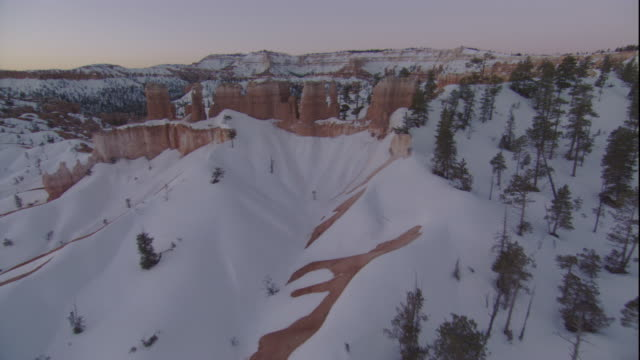 Limestone pinnacles tower in the snow-covered mountains of Bryce Canyon, Utah. Available in HD.