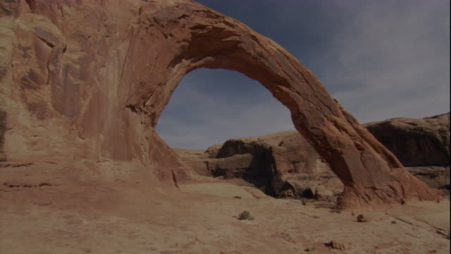 A limestone rock formation creates a natural arch in a Utah desert. Available in HD.
