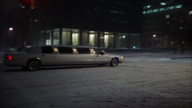 ws pan limousine driving through downtown at night / manhattan, new york, usa - anno 1994 video stock e b–roll