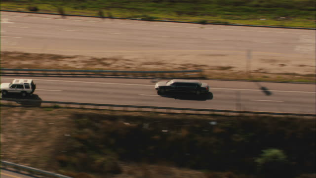 a limousine speeds down a freeway next to a marina in the los angeles area. - limousine luxuswagen stock-videos und b-roll-filmmaterial