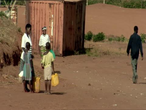 ws limping woman and two children carry water jugs down dirt road / nyamirambo, kigali, rwanda - ルワンダ点の映像素材/bロール