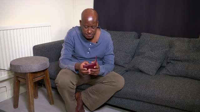 Brother says Met Police must do more to protect victims of domestic violence ENGLAND London INT Various shots of Ivan Kigenza looking at mobile phone