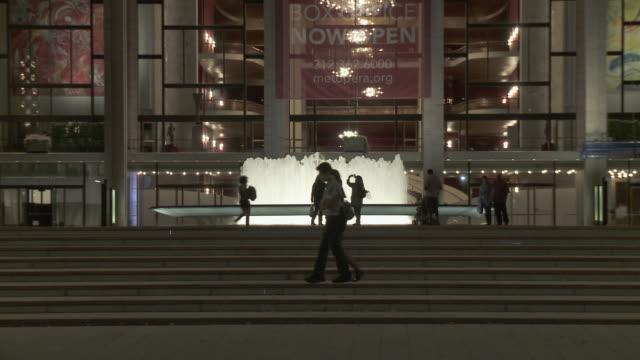 zo ws lincoln center illuminated at night, traffic on street in foreground / new york city, new york, usa - マンハッタン点の映像素材/bロール