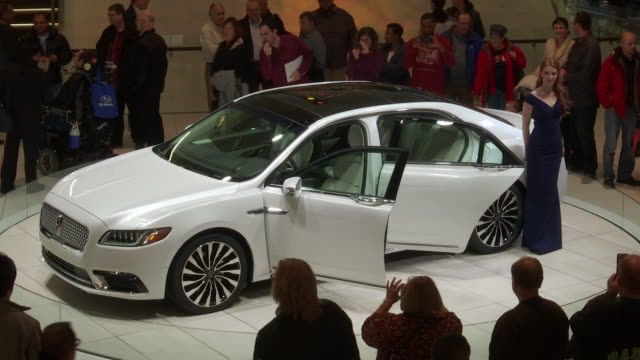 lincoln continental revolving on turntable surrounded by crowd / ws hanging sculpture it opens to reveal car on turntable then closes / pedestal up... - limousine familienfahrzeug stock-videos und b-roll-filmmaterial