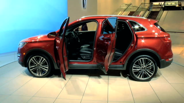 lincoln logo on wall to ws lincoln mkc revolving on turntable / cu lincoln rear license plate passing through frame / ws ruby red mkc revolving on... - crisscross stock videos & royalty-free footage