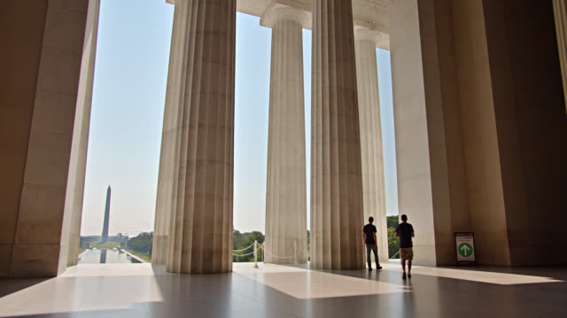 lincoln memorial. washington monument. people walk by. sunset. reflecting pool in distance. - memorial event stock videos & royalty-free footage