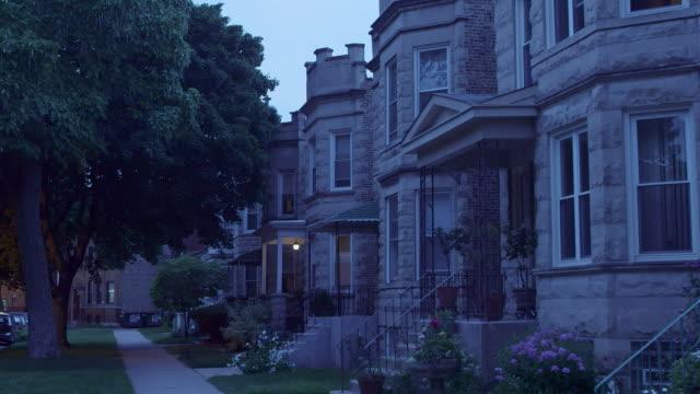 ws pan lincoln square greystone apartments night - villetta a schiera casa video stock e b–roll