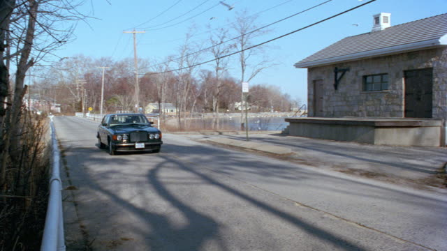 a lincoln town car drives along a lake on long island. - lincoln town car stock videos & royalty-free footage