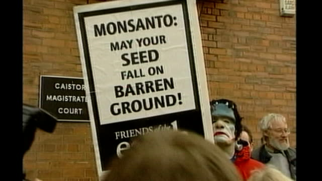 EXT GVs Friends of the Earth demonstrator wearing frankenstein mask holding 'Monsanto May your seed fall on barren ground' placard GV Protestors...