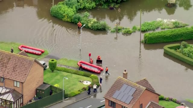 lincolnshire wainfleet all saints flooded fields and village / aerial rescue workers rescued people and rescue dinghy in flooded road / aerial people... - lincolnshire stock videos & royalty-free footage