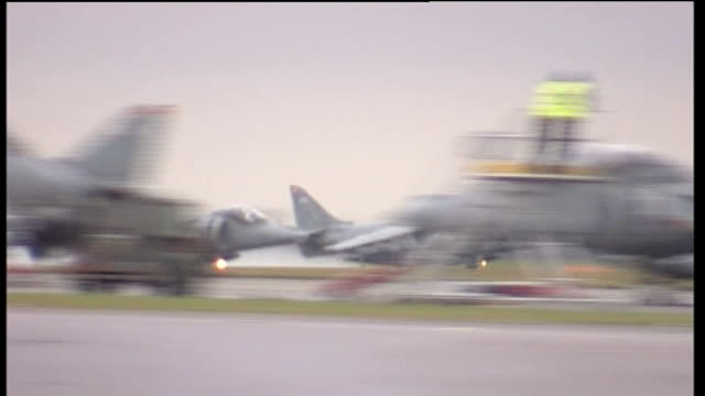 lincolnshire: raf cottesmore: ext two harrier jump jets along runway as take off then flying away - lincolnshire stock videos & royalty-free footage