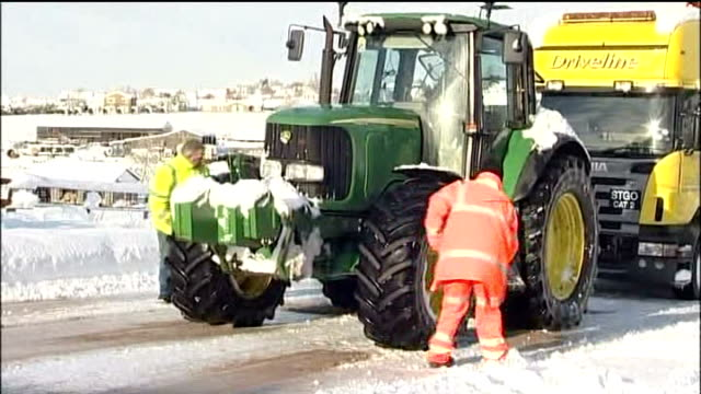 salt being shovelled around tyres of stranded recovery tractor recovery tractor towing lorry - towing stock videos and b-roll footage