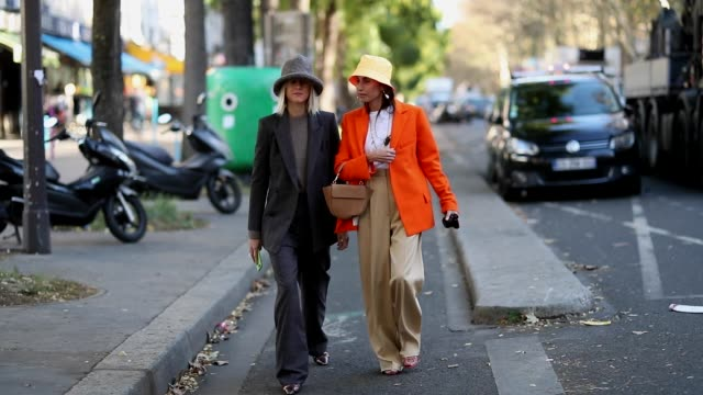 linda tol wearing grey hat and chloe harrouche wearing prada bucket hat and orange blazer is seen outside koche during paris fashion week womenswear... - sonnenhut stock-videos und b-roll-filmmaterial