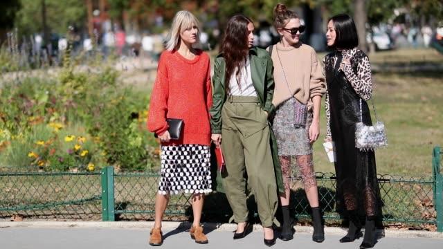 Linda Tol wearing orange red knit Erika Boldrin wearing olive pants green trench coat Madelynn Furlong wearing beige knit silver skirt Tiffany Hsu...