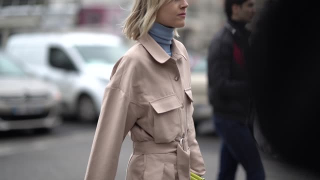 stockvideo's en b-roll-footage met linda tol wears a blue loewe turtleneck a powder pink jumpsuit a lemonyellow wristlet bag black high heeled boots outside nina ricci during paris... - coltrui