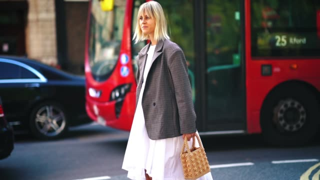 linda tol wears a gray blazer jacket, a white dress, black and white boots, during london fashion week september 2018 on september 15, 2018 in... - gray jacket stock videos & royalty-free footage