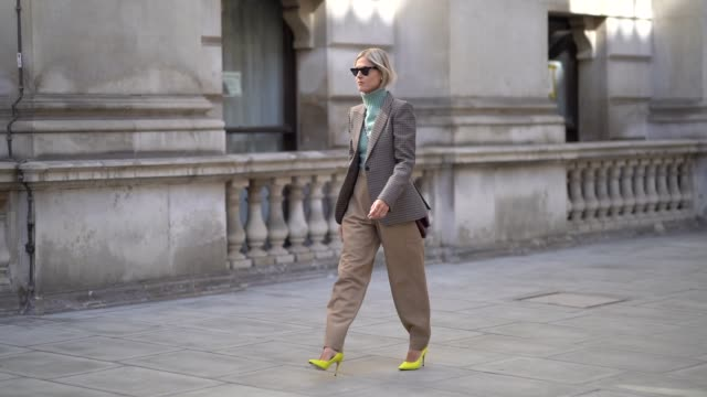stockvideo's en b-roll-footage met linda tol wears sunglasses a blue wool turtleneck pullover a checked pattern print blazer jacket brown large pants yellow shoes during london fashion... - modeweek
