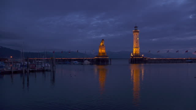 Lindau harbor entrance and lighthouse illuminated, dusk twilight.