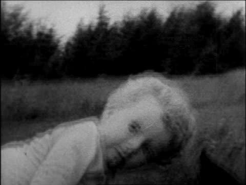 vídeos de stock, filmes e b-roll de lindbergh baby crawling in garden playing with dog / sequence - só bebês meninos