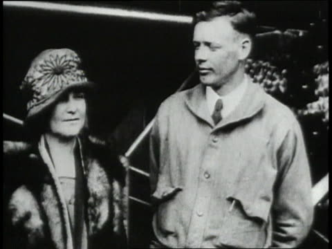 Lindbergh with his mother / airplane being wheeled out of hanger