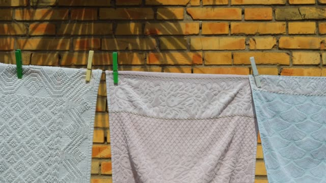 line drying laundry in summertime against a yellow brick wall. real life. - hanging stock videos & royalty-free footage