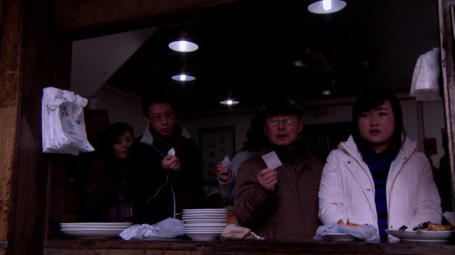 MS Line o people waiting and holding their receipts for Chinese dumplings, chef preparing dumplings in foreground, Changsha, Hunan, China