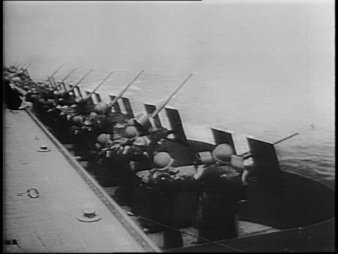 line of antiaircraft gun crews fire from ship / japanese torpedo bomber planes attack us navy fleet / planes hit by tracer fire fall burning into sea... - flugabwehr stock-videos und b-roll-filmmaterial