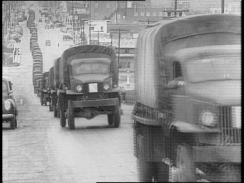 line of army trucks driving down road / montage of picket line in front of the federal motor truck co factory in detroit, mi / men gathering outside... - 1941年点の映像素材/bロール