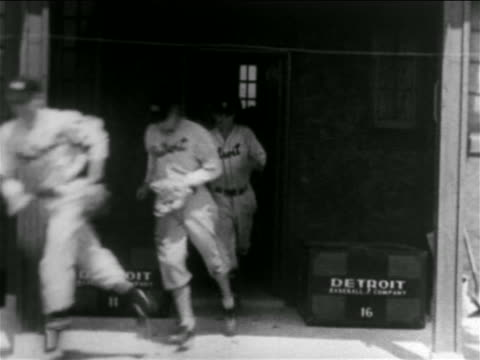 vídeos de stock e filmes b-roll de b/w 1938 line of baseball players in uniforms running out of building - camisola de basebol