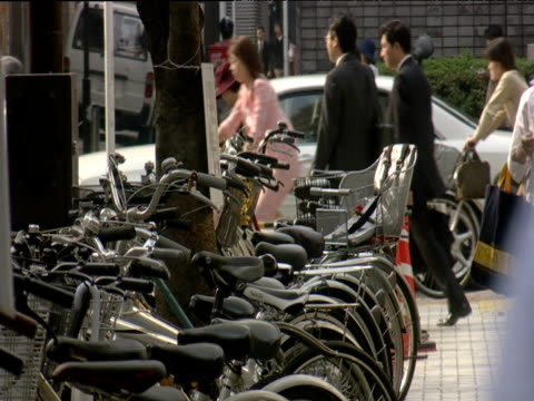 vidéos et rushes de line of bicycles parked on pavement as pedestrians and traffic pass by - 1990 1999